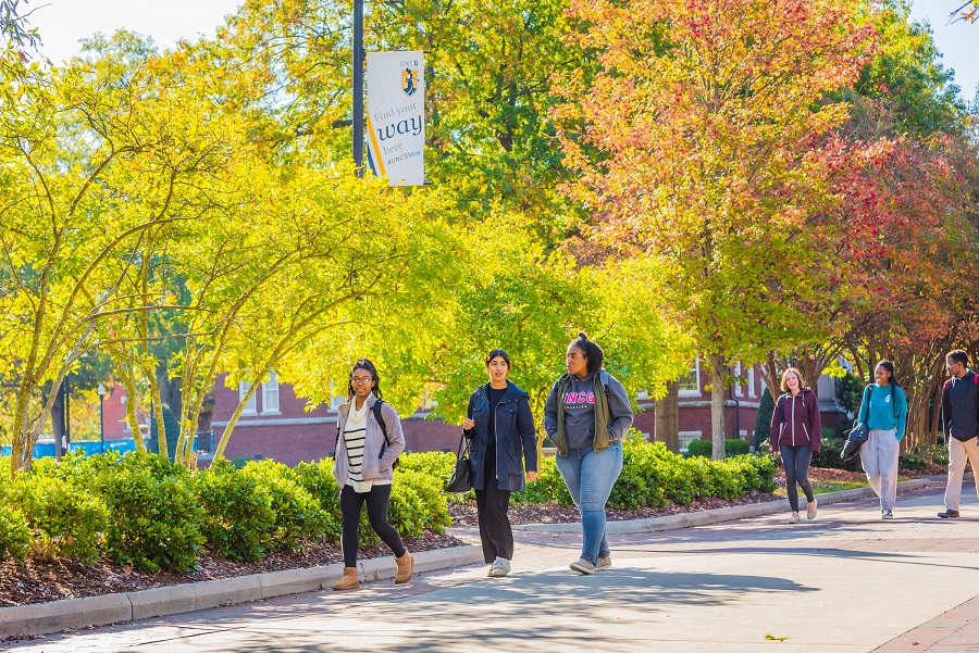 Students walking on College Avenue with fall foliage in the background